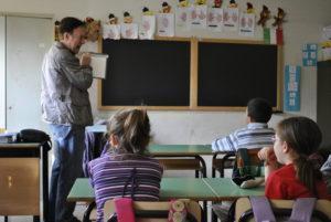 Un uomo mostra una tavoletta braille a una classe di scuola elementare